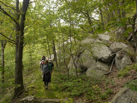 Hikers pass by rock formations on the Fishkill Ridge Trail